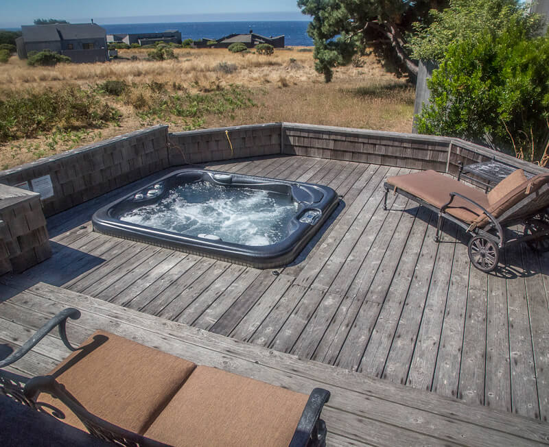 Deck with hot tub, a chaise lounge, love seat and view across meadow to the ocean.
