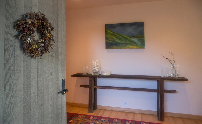 Entry vestibule, table and painting on wall.