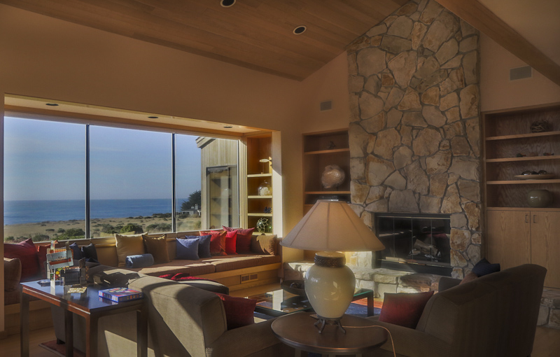 Living room with fireplace, window seat and ocean view.