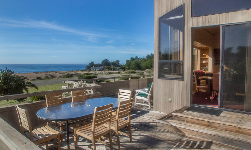 Back deck with glass table, six chairs and view of ocean.