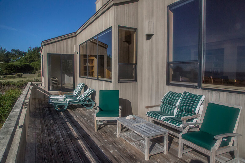 Front deck with four chairs, coffee table and two chaise lounges.
