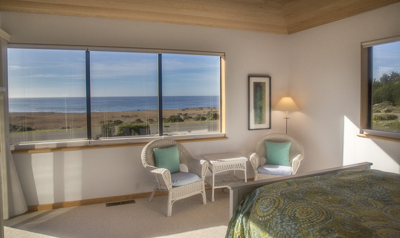 Bedroom with bed, two chairs, small table and ocean view.