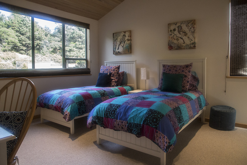 Bedroom with twin beds, side table, lamp and ottoman.