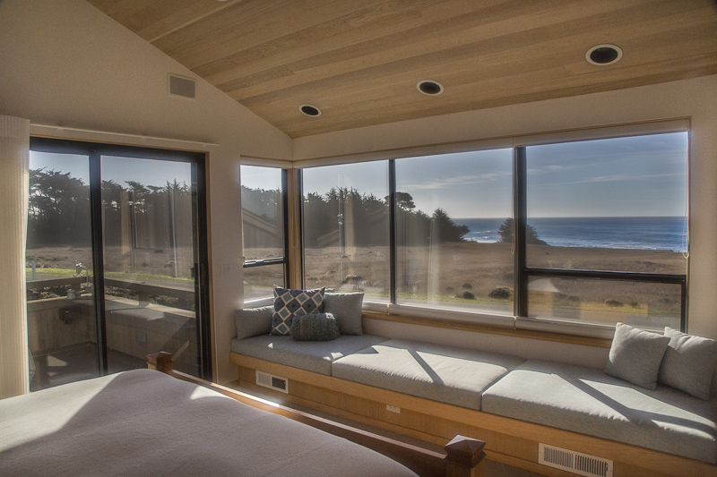 Bedroom with window seat and ocean view.
