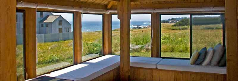 Window seat in the living room with a view across the meadow to the ocean.