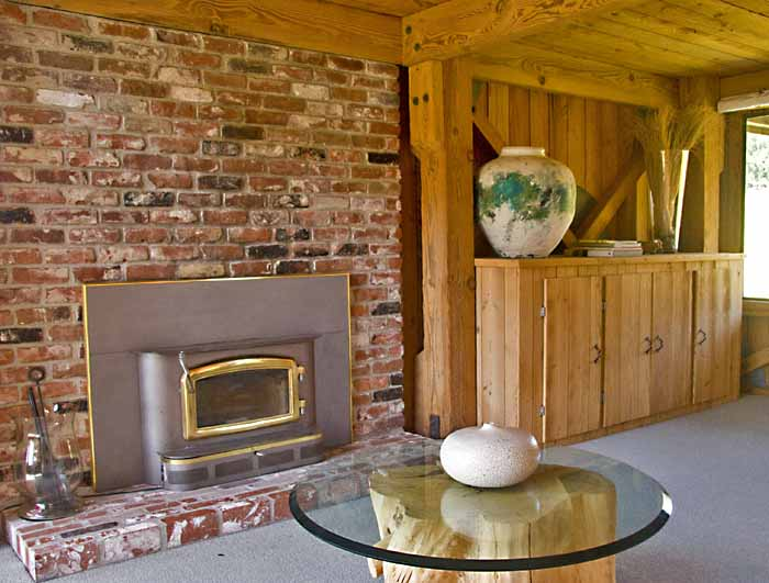 Small circular glass table, fireplace and cabinet with a large ceramic pot on it.