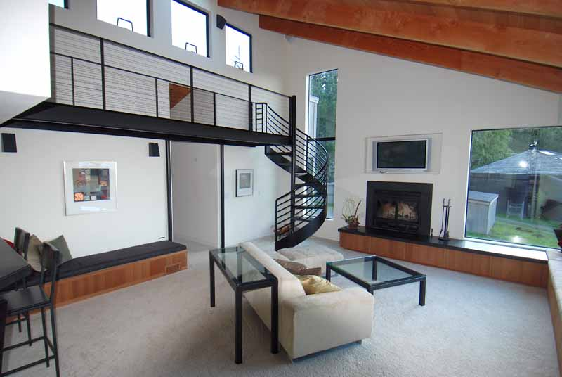 Living room showing sofa, glass top coffee table, glass top table, fireplace, chef's bar, two stools, metal balcony with circular metal stairway.