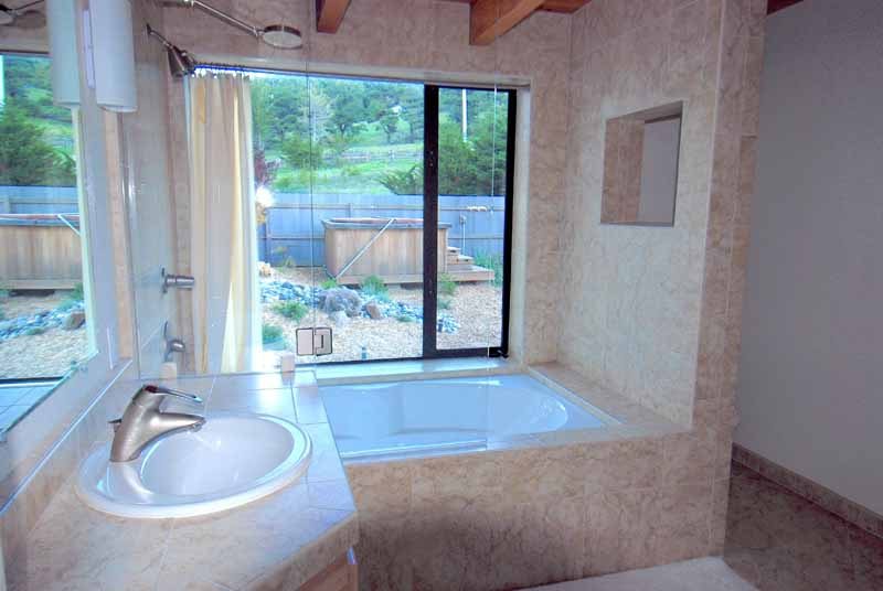 Bathroom showing sink and tub with view of hot tub and garden.