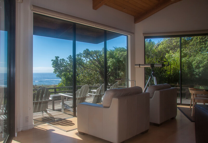 Living room - two chairs and telescope with view of ocean