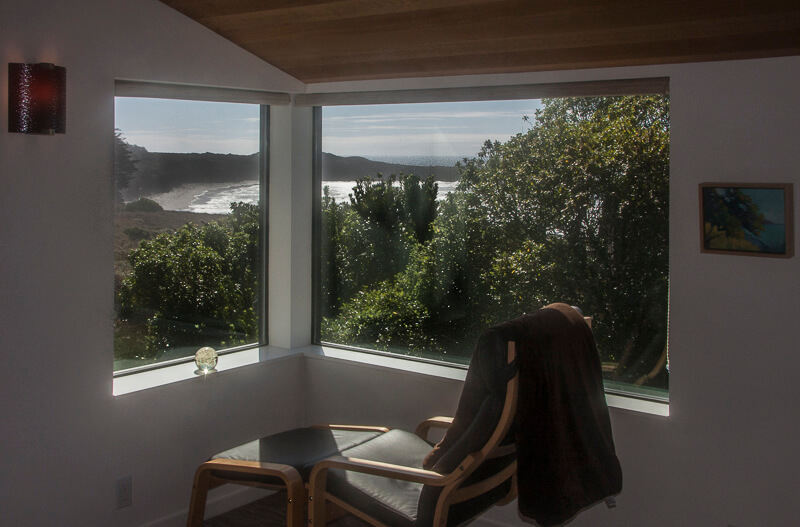 chair in front of window with view of ocean