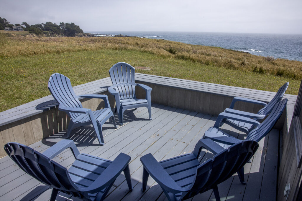 Outside deck with six chairs and views across the meadow to the ocean