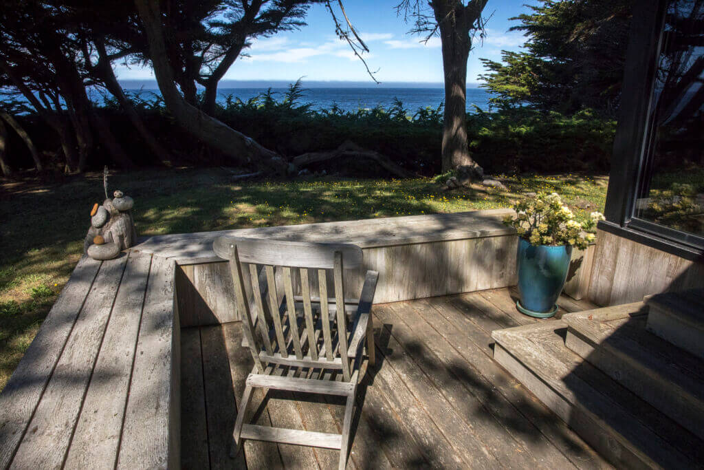 Outside deck with chair and view of ocean.