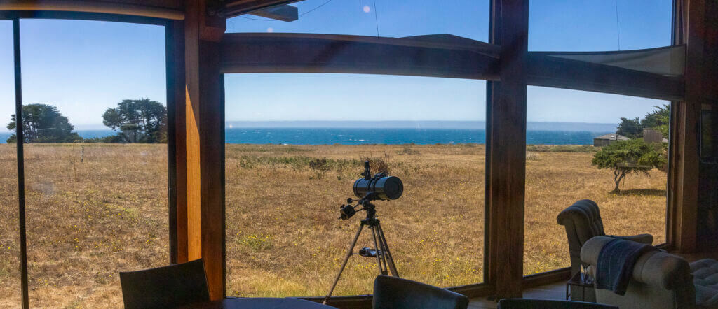 the view of the ocean from the dining room with a telescope in the center of the window.