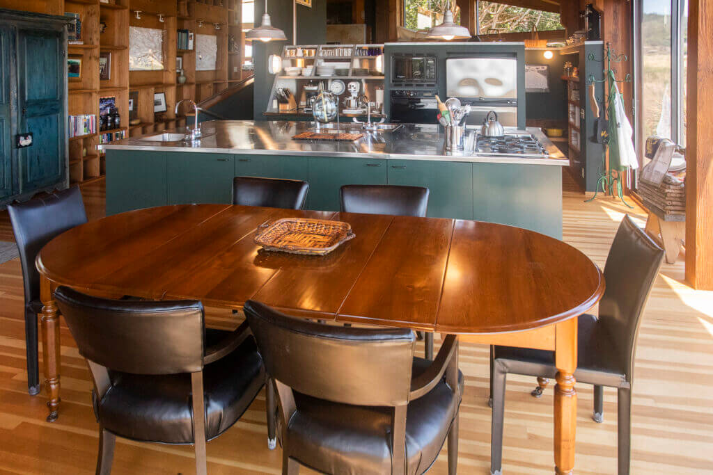 The dining rooms table with six chairs and the kitchen in the background.