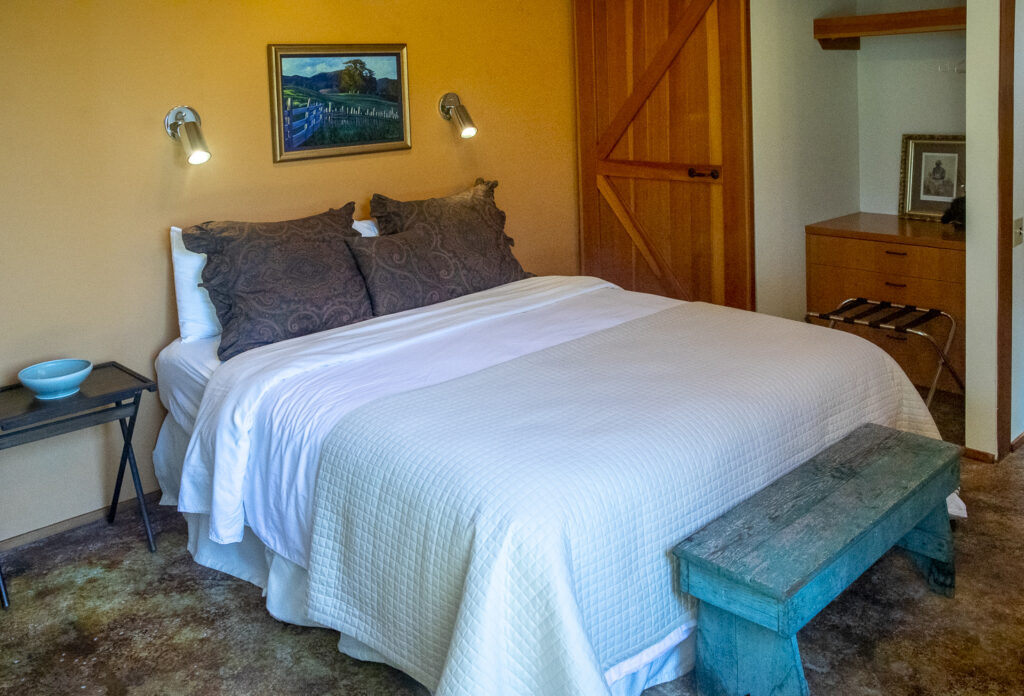 One of two guest bedrooms showing the bed and a small bench.