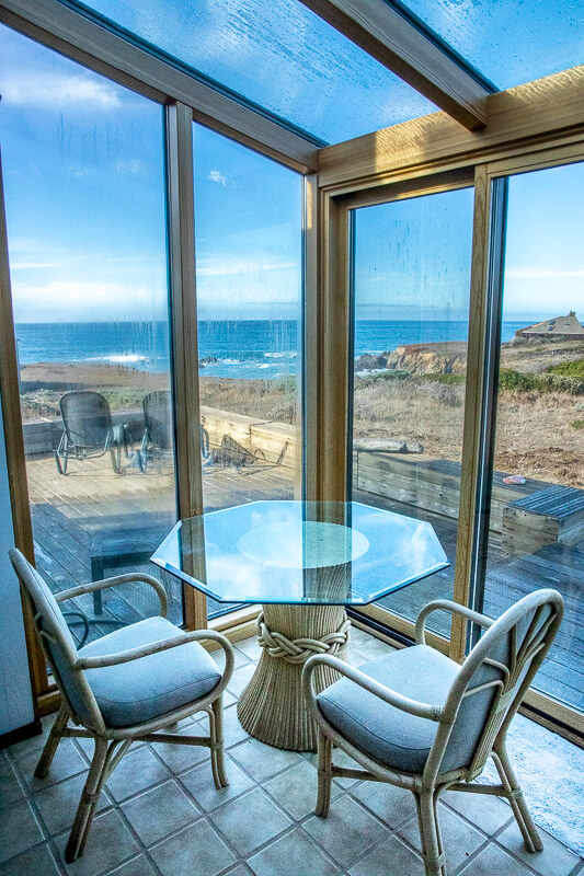 Glassed in porch with table and two chairs and view of deck and ocean beyond.