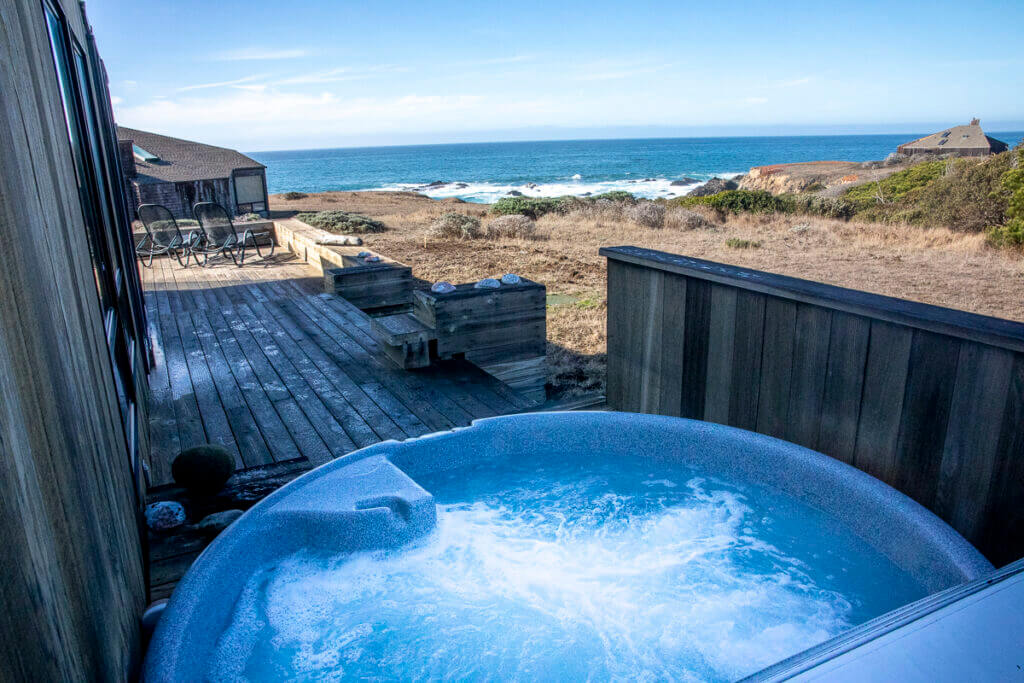 A hot tub on the deck with a view of the ocean beyond.