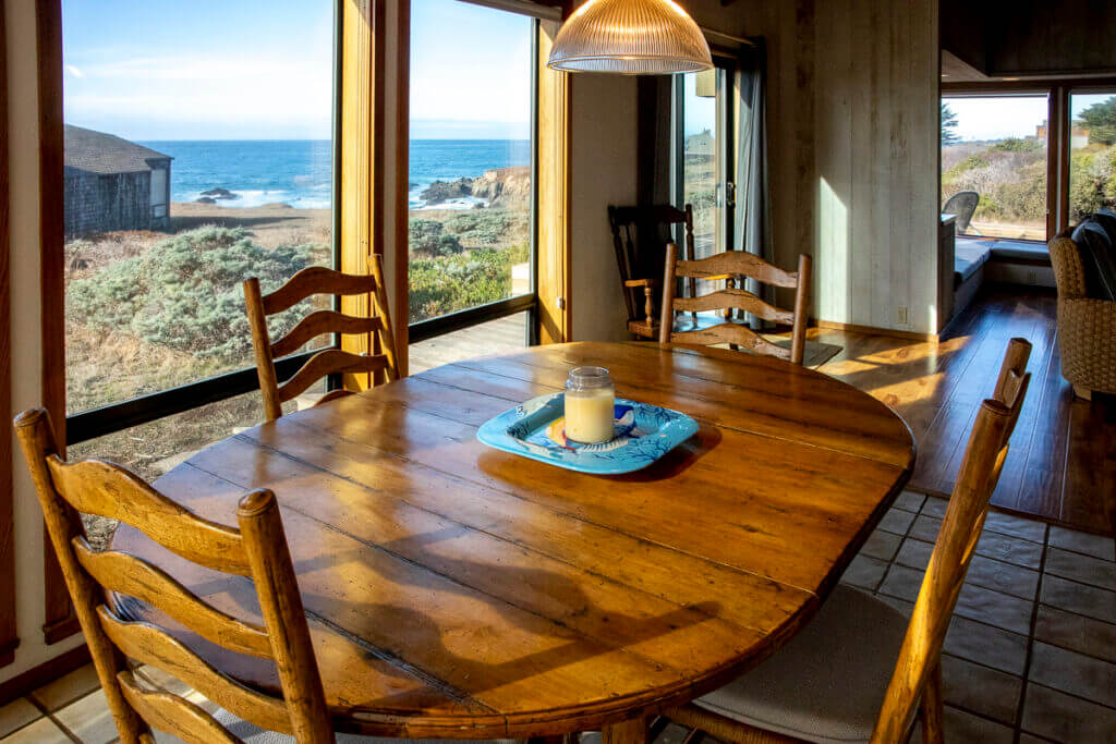Dining room table and four chairs with view of ocean beyond.