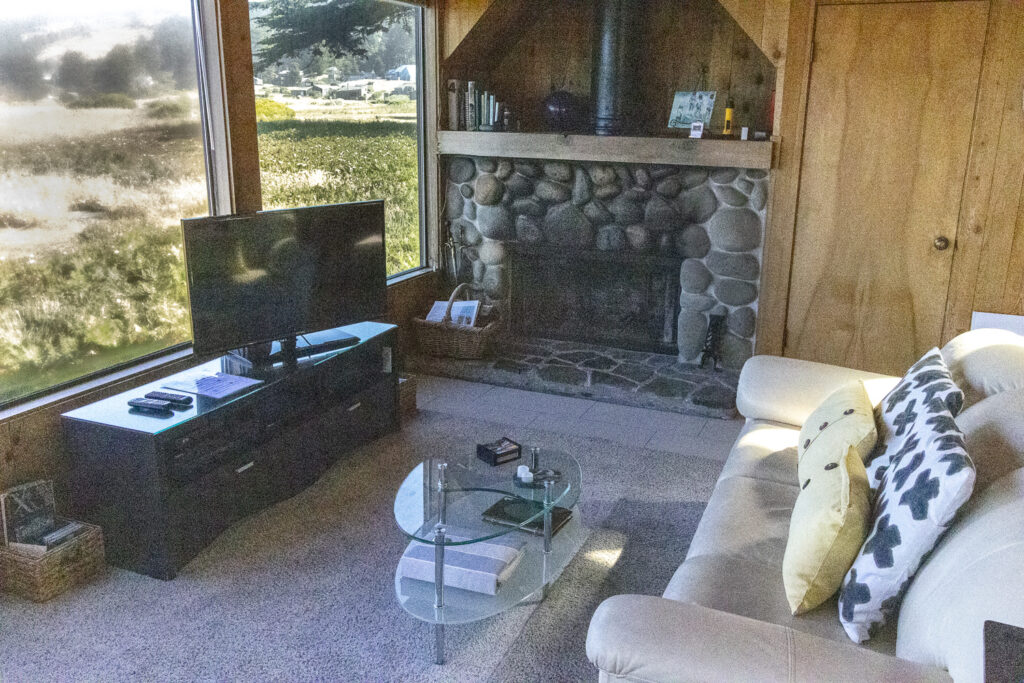 Fireplace and television in front of couch.